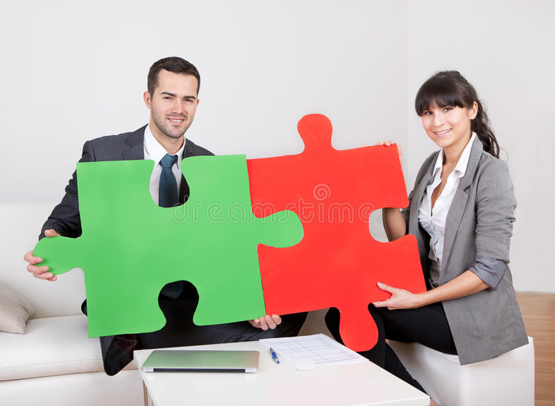 Two business people connecting puzzle pieces royalty free stock photography