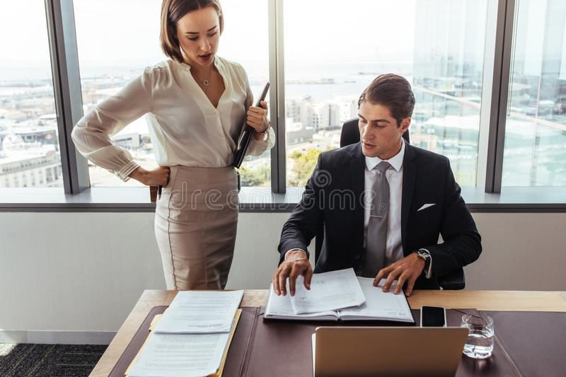 Business people discussing contract documents in office stock image