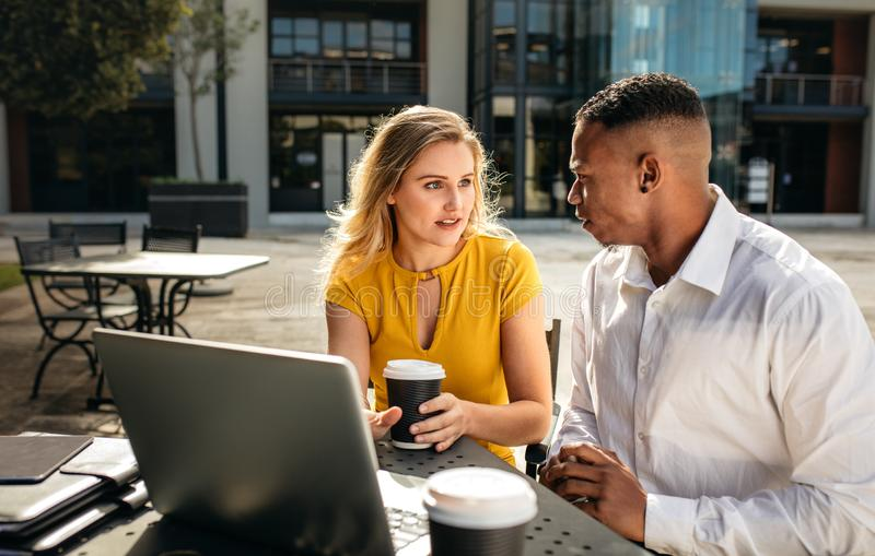 Two business people discussing work at office cafeteria. Two business people talking while sitting at office cafeteria. Business women with men sitting outdoors royalty free stock image