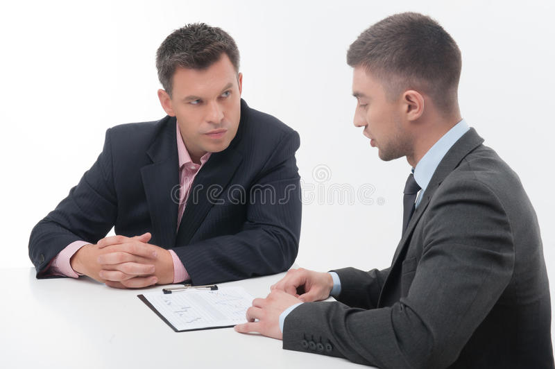 Two business people in elegant suits, chief and. Two business people in elegant suits, chief looking precisely at employee, holding clipboard with papers royalty free stock photo