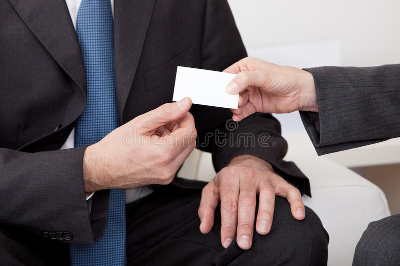 Two business people exchanging visiting card. At the meeting royalty free stock photos