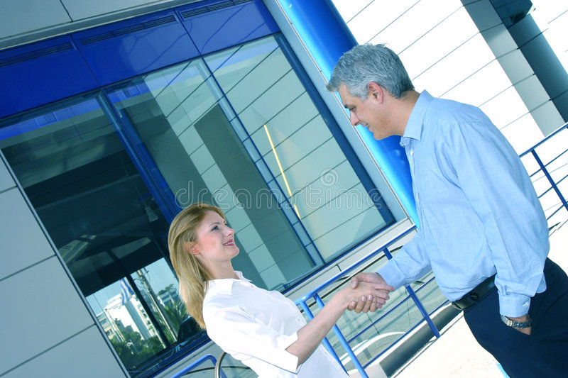 Two Business People Greet. Two casually dressed business people, meet each other for the first time with a warm handshake. Diagonal perspective - color digitally royalty free stock photo