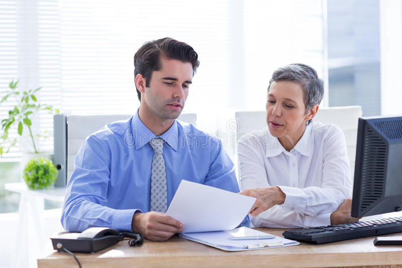 Two business people looking at a paper while working on folder stock images