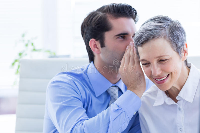 Two business people looking at a paper while working on folder. In the office stock photo