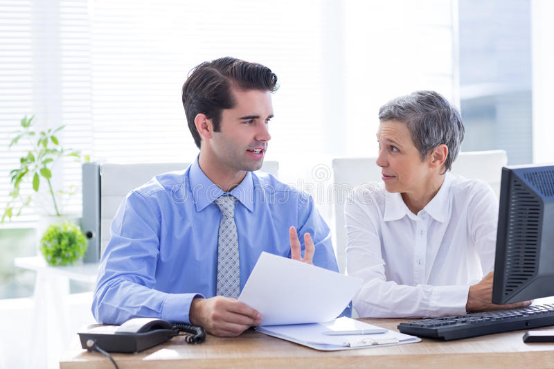 Two business people looking at a paper while working on folder. In the office royalty free stock photos