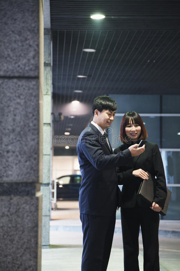 Download Two Business People Looking At Phone In A Parking Garage, Beijing Stock Image - Image: 36767319