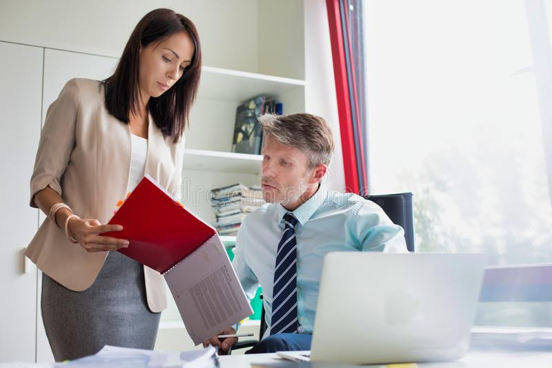 Two business people looking a red file in a small office in a real life business. Photo of Two business people looking a red file in a small office in a real stock photography