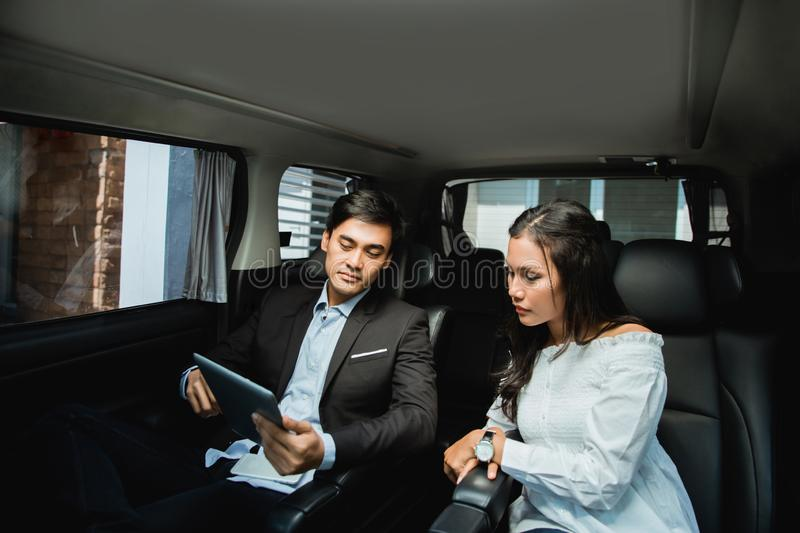 Two business people meeting while sitting on passenger seat of car stock photography