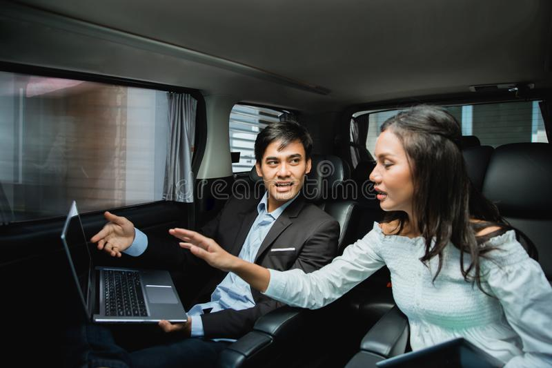 Two business people meeting while sitting on passenger seat of car stock photo
