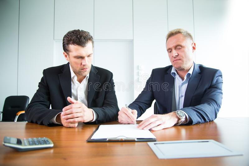 Two business people signing a document. At conference table stock images