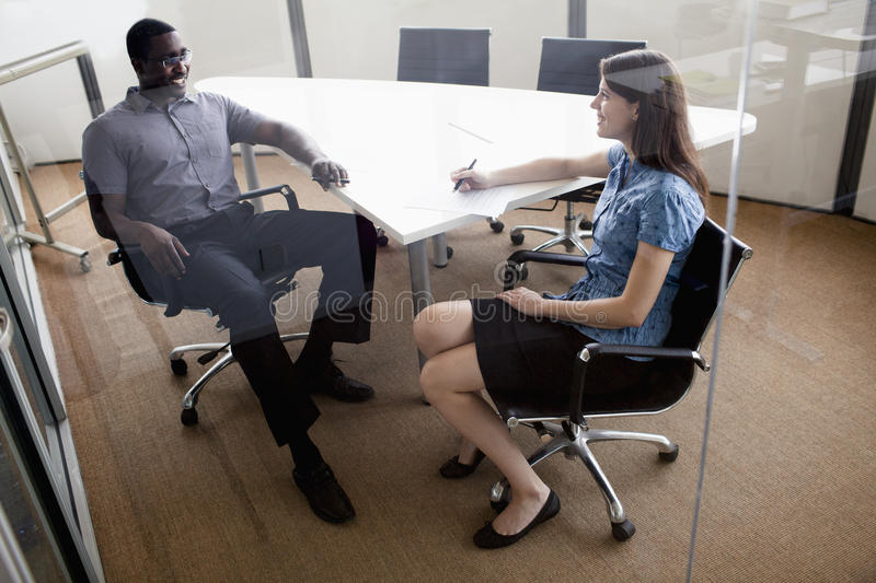 Two business people sitting at a conference table and discussing during a business meeting stock image