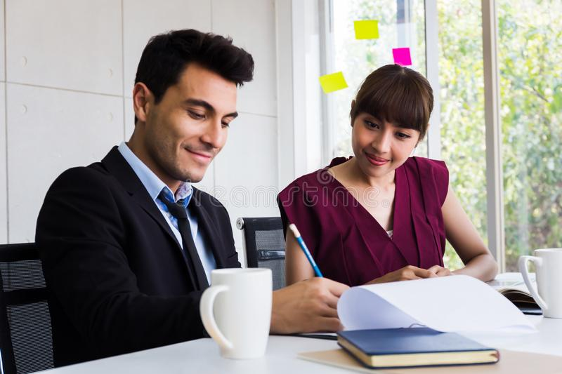 Two business people taking notes together in meeting stock image