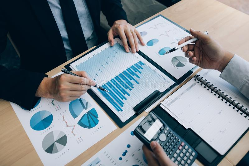 Two business people talking about graph and analysis about finance budget company and using calculator in office room royalty free stock photos