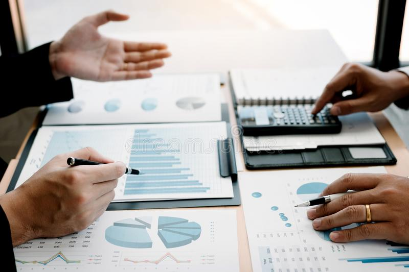 Two business people talking about graph and analysis about finance budget company and using calculator in office room stock image