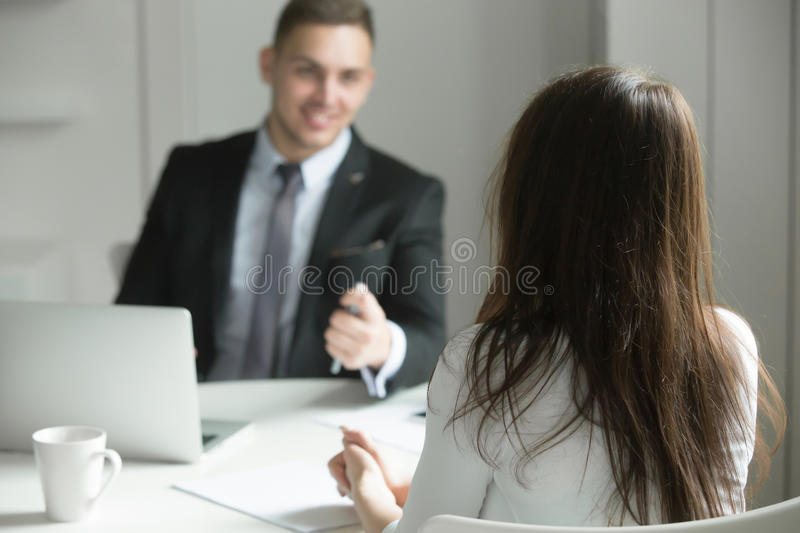 Two business people talking at the office desk stock photography