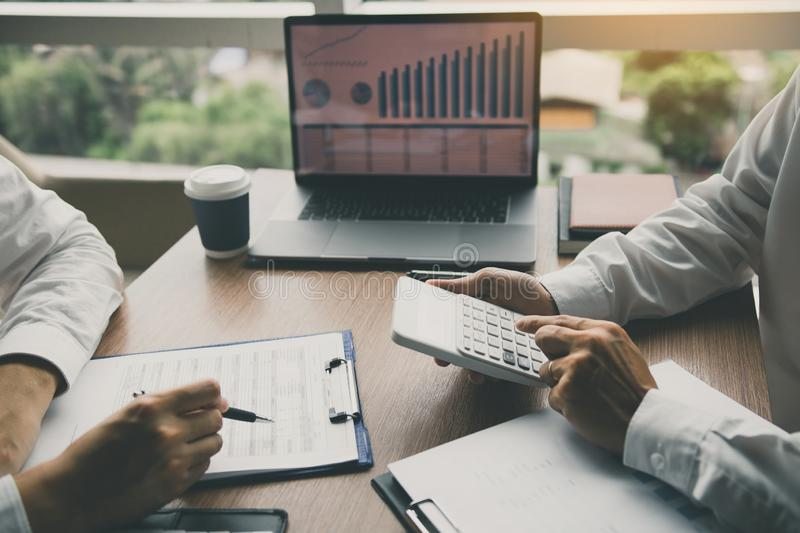 Two business people talking about report graph and analysis about finance budget or cost company and using calculator in office royalty free stock image