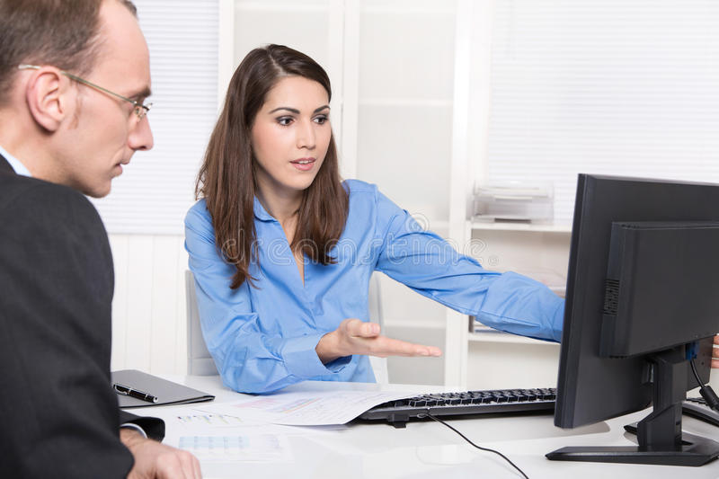 Two business people talking together at desk - adviser and customer. Or recruitment royalty free stock images