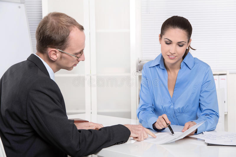 Two business people talking together at desk - adviser and customer. Or recruitment stock photos