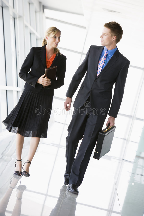 Two business people walking in corridor talking royalty free stock images