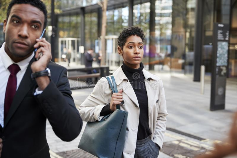 Two business people walking in a street in the city of London, man using smartphone and woman carrying a bag, selective focus stock photo