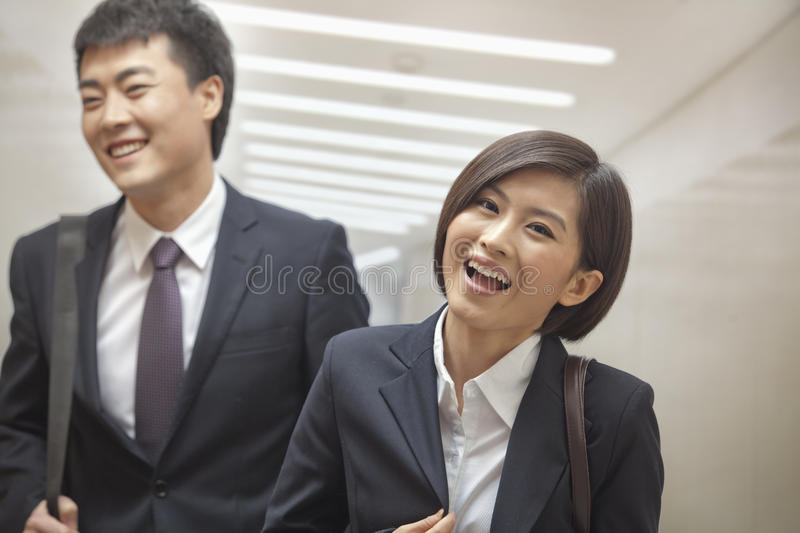 Two Business People Walking Together, Smiling and Laughing, Indoors stock images