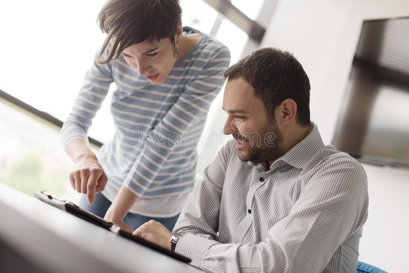 Two Business People Working With Tablet in startup office stock photography