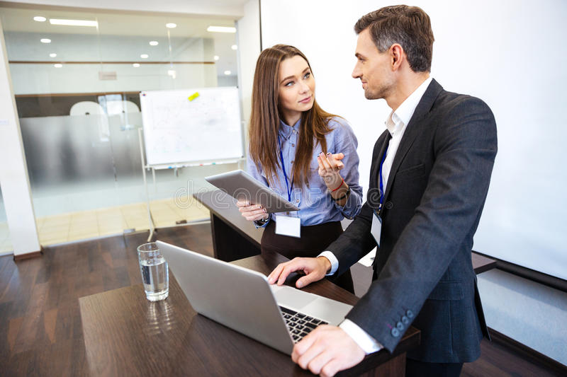 Two business people working together uing laptop and tablet stock images