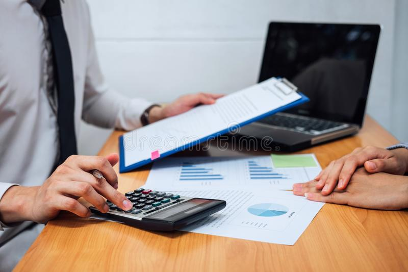Two business team working and discussing Financial investment on report with calculate Analyze business and market growth on. Financial document data graph and stock image