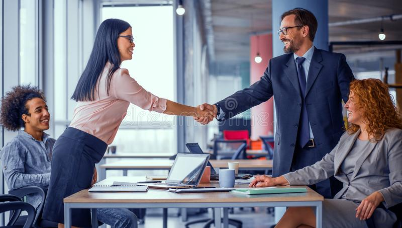 Two business teams successfully negotiating, shaking hands. At meeting table business groups shaking hands on completed deal. Man and women handshake. Toned stock photography