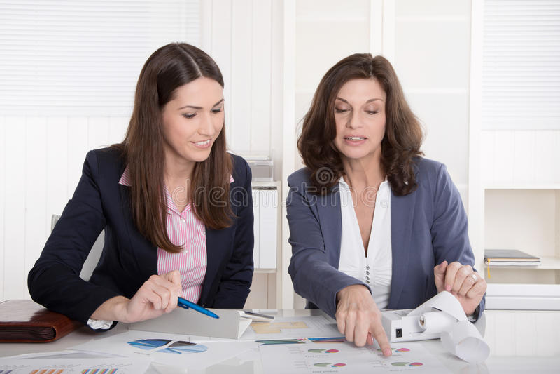Two business woman analyzing balance sheet. Two business women analyzing balance sheet sitting at desk royalty free stock image