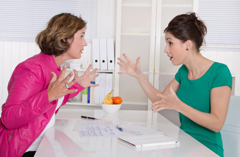 Two business woman disputing in the office having disagreement. stock photography