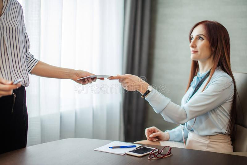 Friendly female boss gives a note to her assistant girl discussing tasks in the office. stock photo