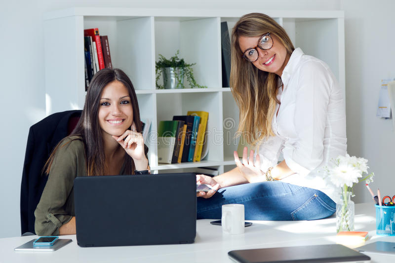 Two business woman working in her office. Portrait of two business women working in her office stock photo
