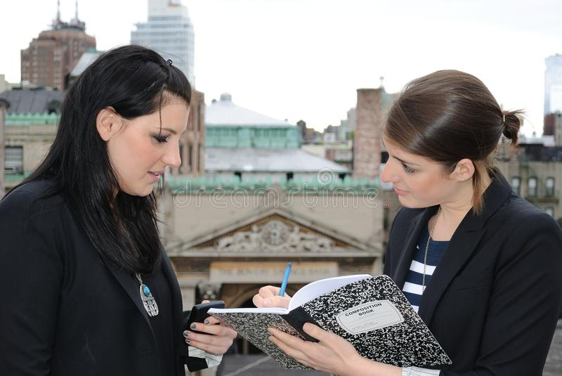 Two Business Women. One girl writes while the other dictates stock photo