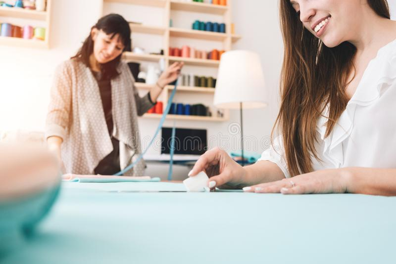 Two business women create concept new clothing in sewing studio. Small production stock photo