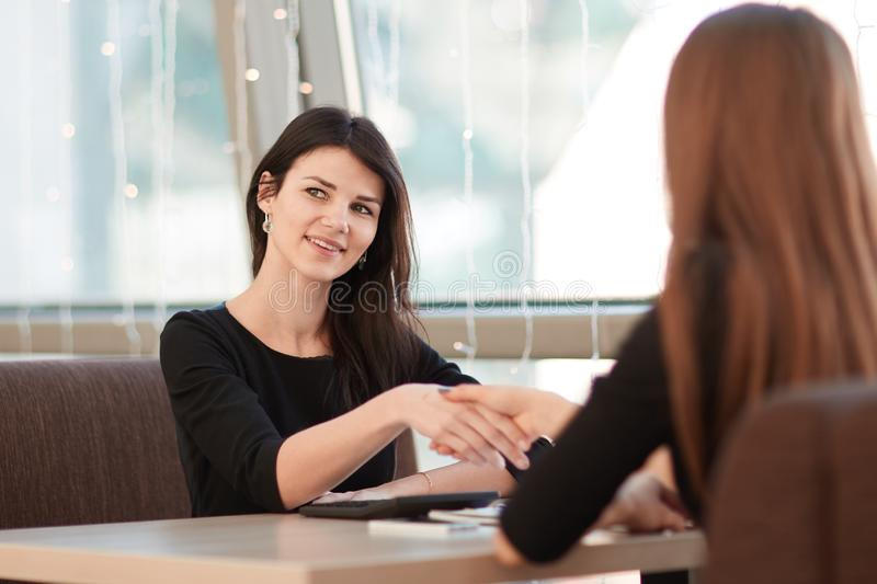 Two business women shaking hands at an informal meeting. Concept of cooperation royalty free stock photos