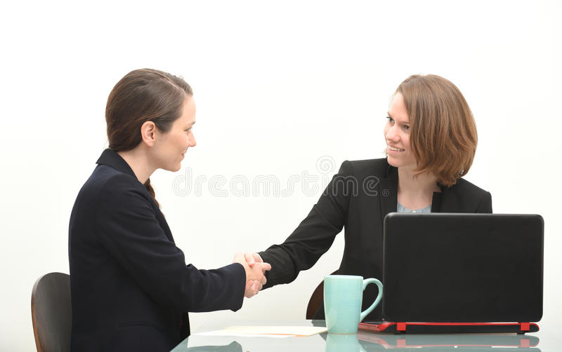 Two business women shaking hands stock photography