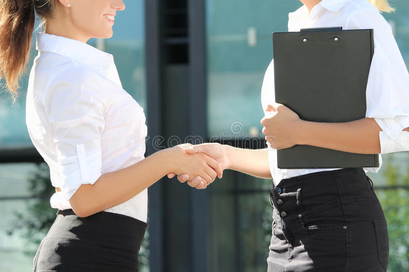 Two business women shaking hands in street royalty free stock photos