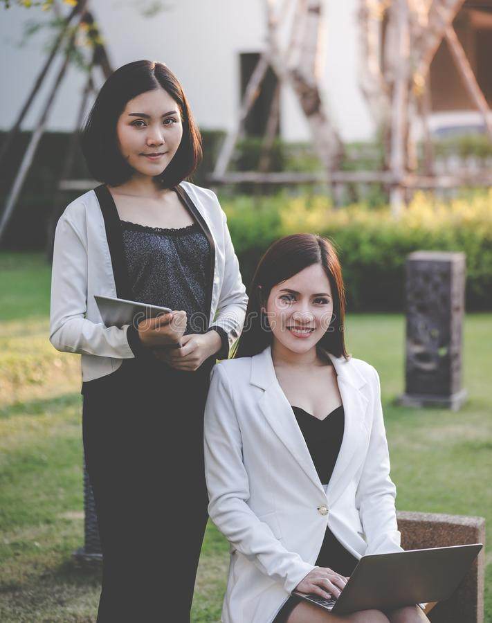 Two business woman sitting in park royalty free stock images