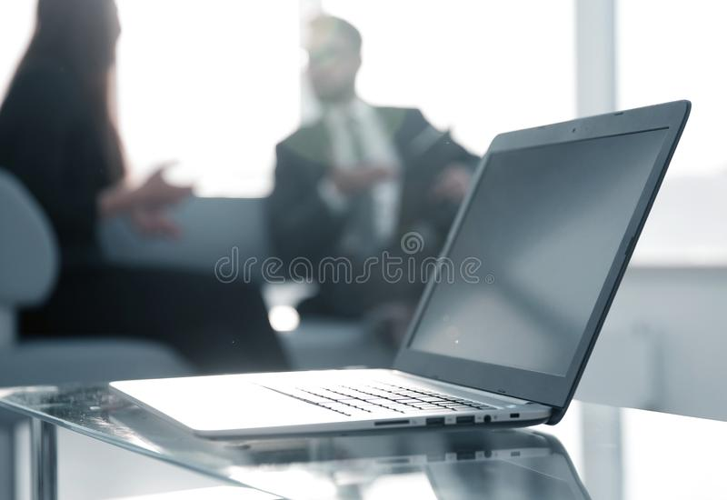 Focus on laptop on the table. Blurred people on background. stock image