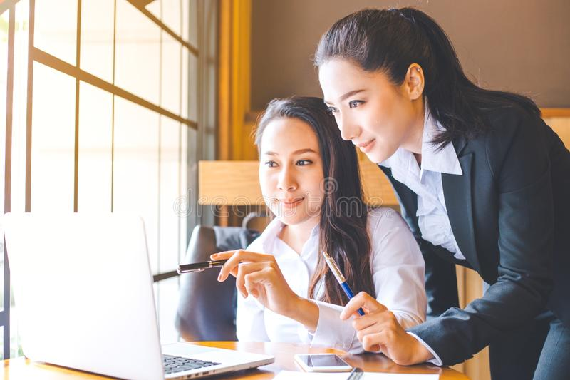 Two business women are working on a notebook computer, holding a stock image
