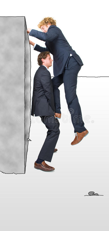 Two businessman. Helping each other climb a platform, illustrating the overcoming of obstacles with teamwork royalty free stock image