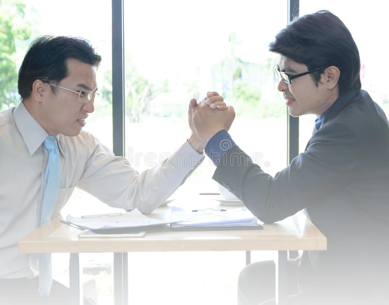 Two Businessman arm-wrestle. In coffee shop royalty free stock photo