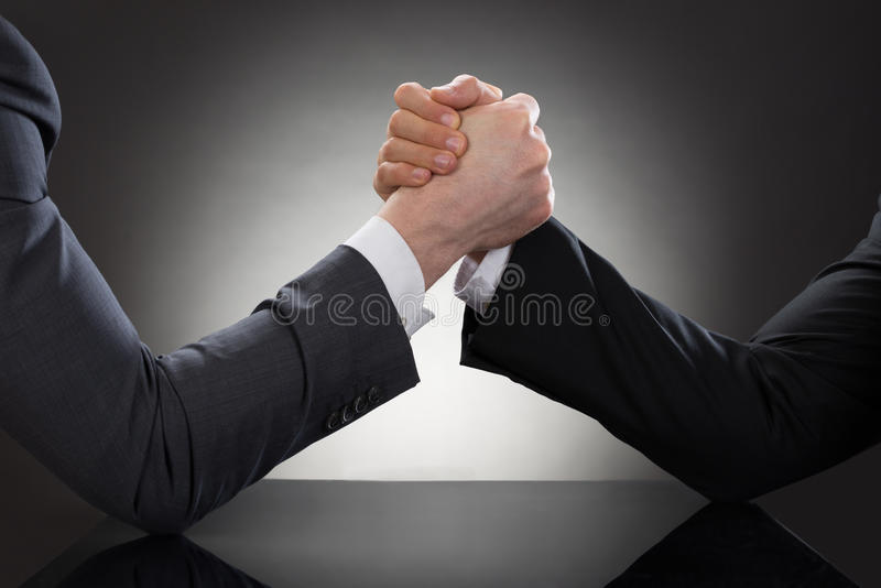 Two businessman arm wrestling. Close-up Of A Two Businessman Competing In Arm Wrestling stock image