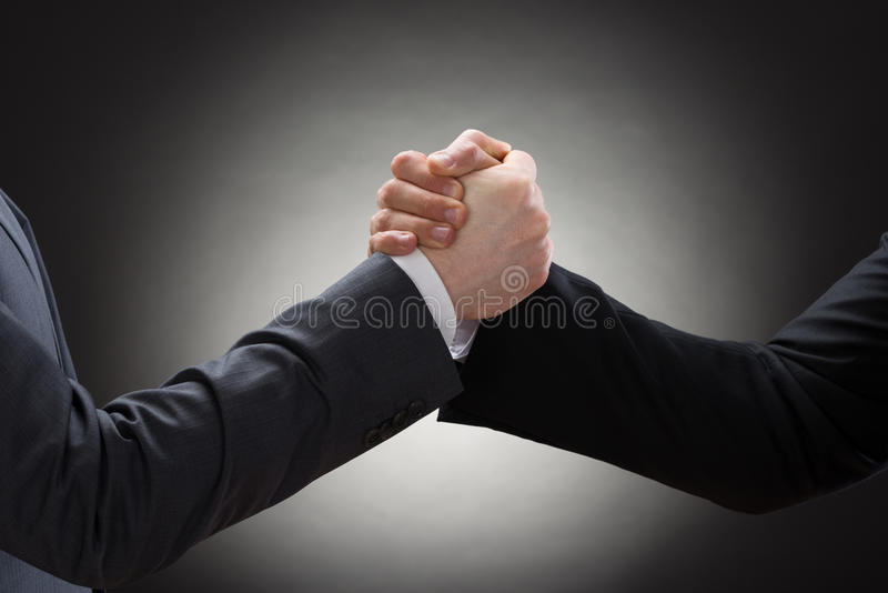 Two businessman arm wrestling. Close-up Of A Two Businessman Competing In Arm Wrestling royalty free stock photo