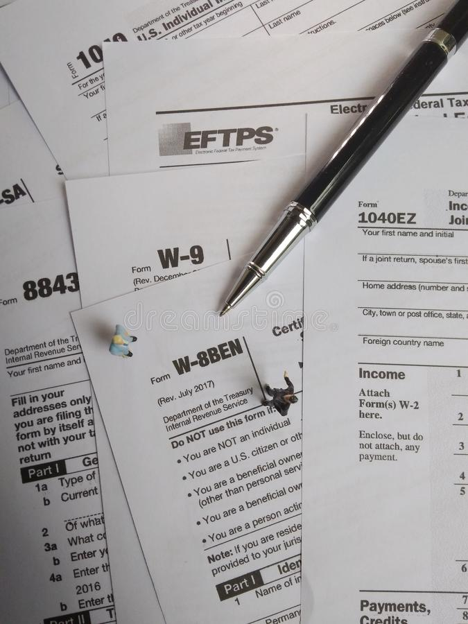 Two businessman discussion about usa tax form, w-8ben, certificate of foreign status of beneficial owner for united states tax wit. Photo two businessman stock photos