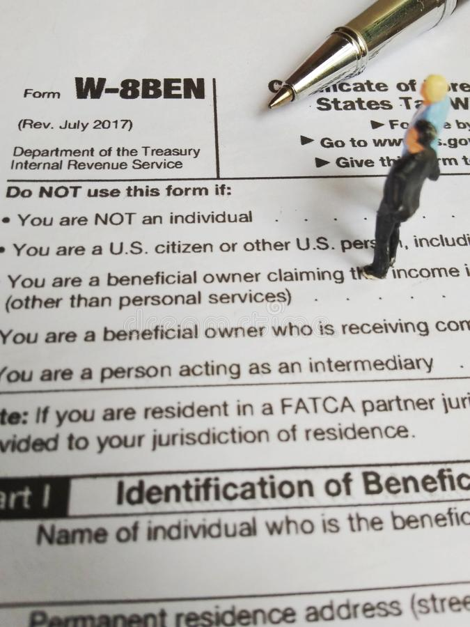 Two businessman discussion about usa tax form, w-8ben, certificate of foreign status of beneficial owner for united states tax wit. Photo two businessman royalty free stock photography