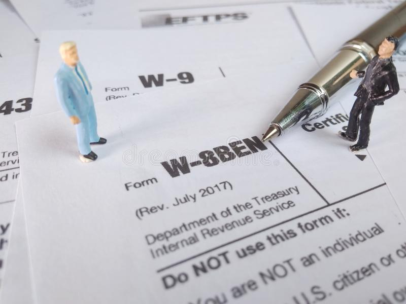 Two businessman discussion about usa tax form, w-8ben, certificate of foreign status of beneficial owner for united states tax wit. Photo two businessman stock photo