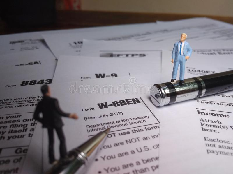 Two businessman discussion about usa tax form, w-8ben, certificate of foreign status of beneficial owner for united states tax wit. Photo two businessman royalty free stock images