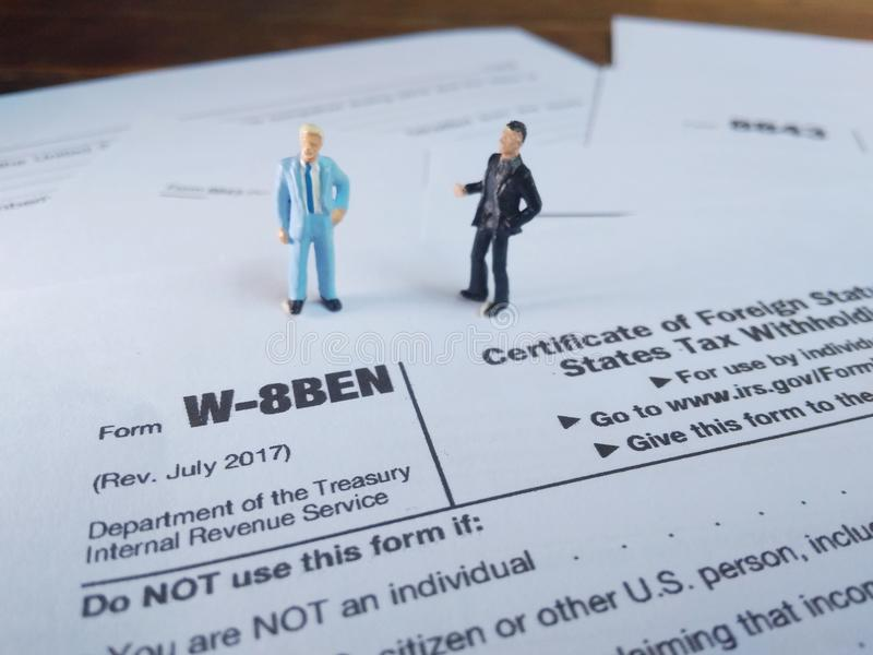 Two businessman discussion about usa tax form, w-8ben, certificate of foreign status of beneficial owner for united states tax wit. Photo two businessman royalty free stock photo